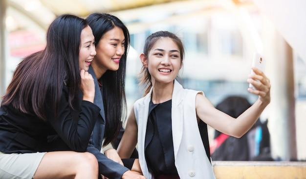 Три счастливые офисные девушки, глядя на смартфон и принимая селфи перед офисным зданием