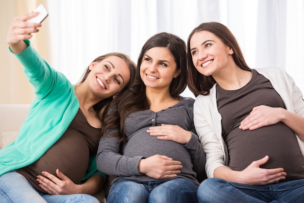 Three happy pregnant women are making selfie.