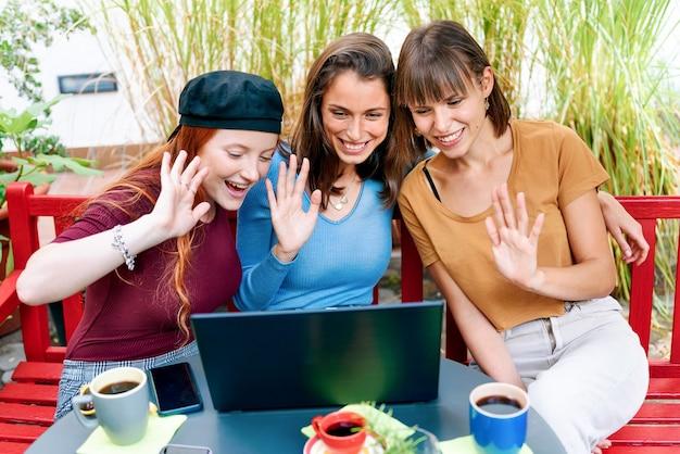 세 명의 행복한 미소 짓는 젊은 여성이 노트북 컴퓨터로 화상 통화를 하며 장거리 통신을 위해 화면에서 인사를 하고 있다
