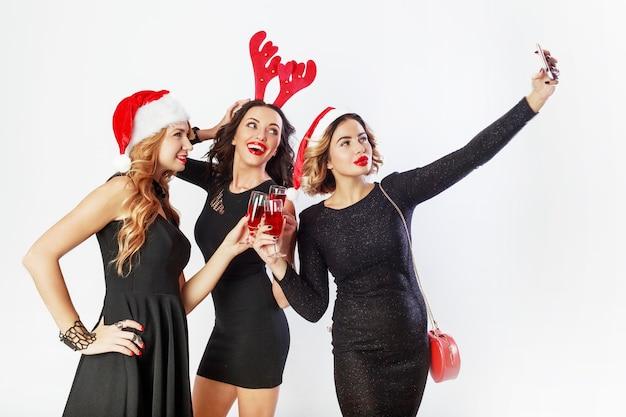 Tre ragazze alla moda felici che trascorrono del tempo alla festa pazza, ballando, divertendosi e ridendo. indossare abiti casual eleganti, cappelli in maschera di capodanno. fare foto.