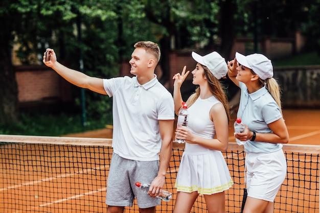 세 명의 행복한 테니스 선수가 셀카를 만듭니다.