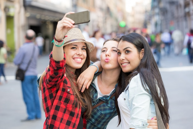 Three happy women taking a selfie in the city