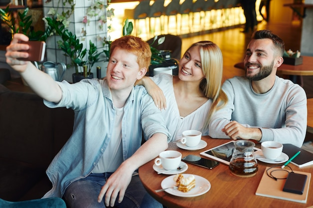 Three happy young affectionate friends looking at smartphone camera while making selfie in cozy cafe by cup of tea