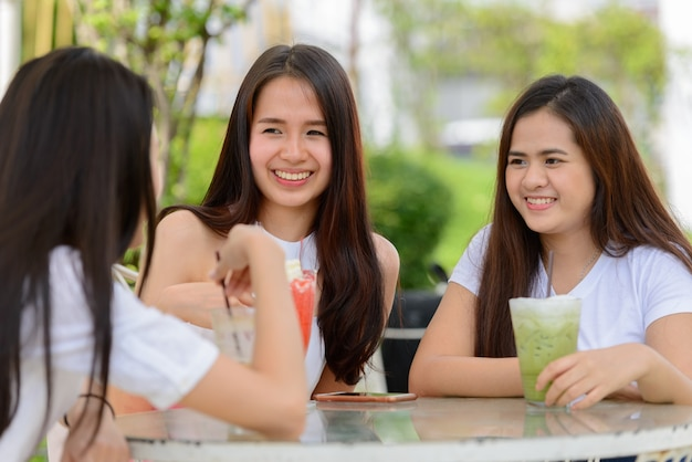 屋外の喫茶店で一緒に座っている友人として3人の幸せな若いアジアの女性