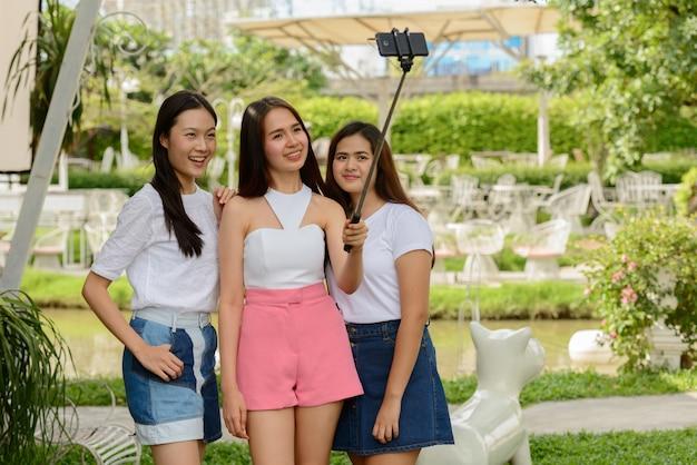 自撮りで携帯電話で自撮りをしている友人として3人の幸せな若いアジアの女性が屋外の自然の中で一緒に固執