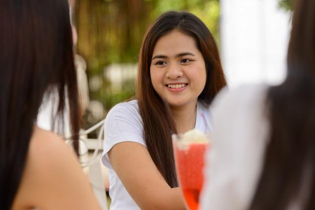 屋外の喫茶店で一緒に友達として3人の幸せな若いアジアの女性