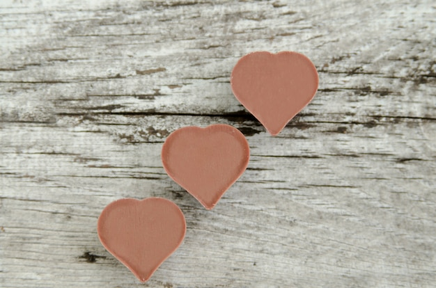 Three heart shape chocolate on white rustic table.top view,empty space for text.