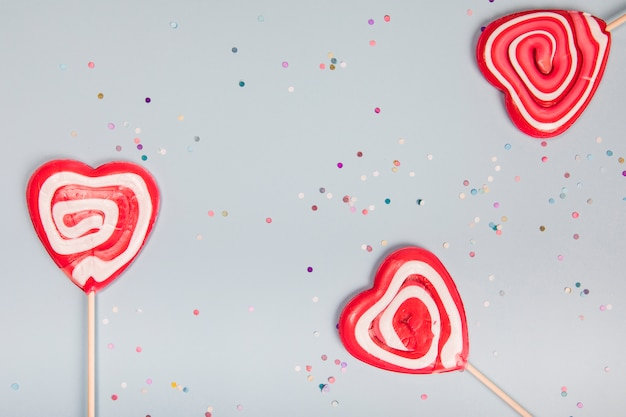 Three heart shape red lollipops on gray background with colorful confetti