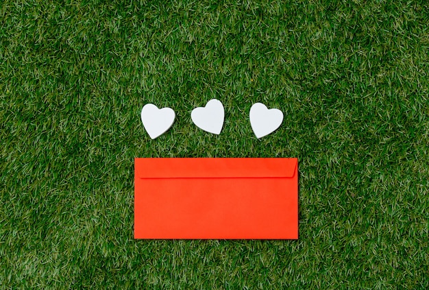 Three heart shapes and red envelope on green grass.