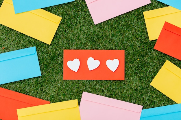 Three heart shapes and red envelopes on green grass.