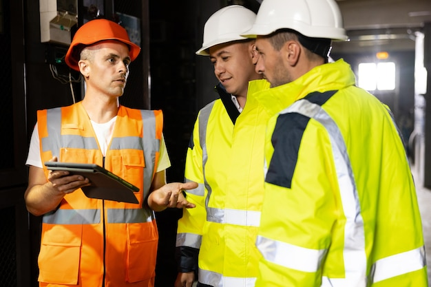Три инженера тяжелой промышленности и рабочий стоят на заводе по производству труб с цифровым планшетом