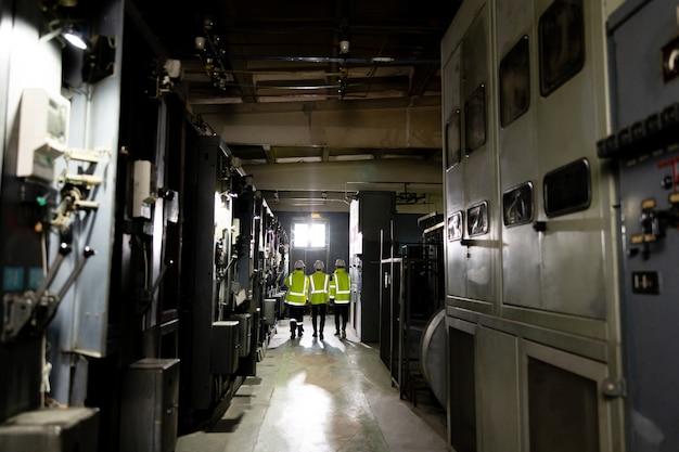 ヘルメットをかぶった3人の重工業エンジニアが鉄鋼金属製造工場とdiscuを歩きます