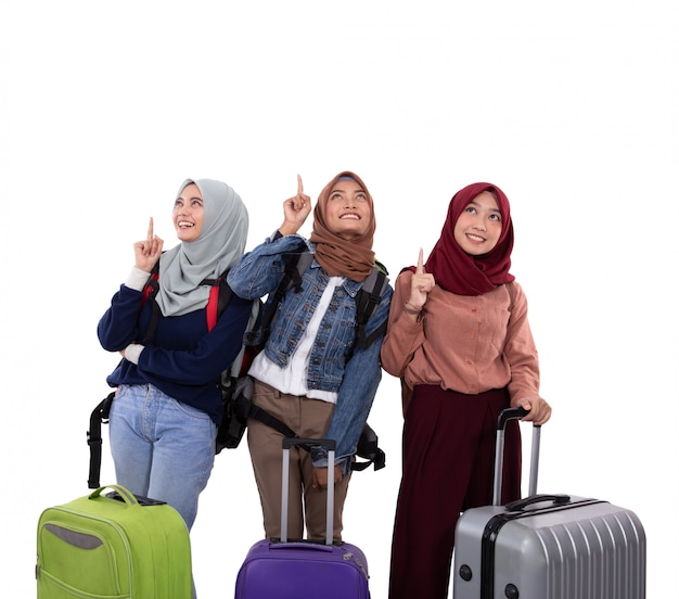 Three hijab woman standing holding suitcase and carrying bag with hands pointing