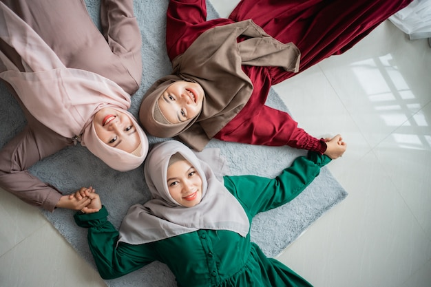 Three hijab women smiled while laying on the mattress