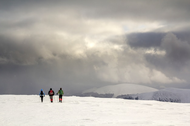 Three hikers in bright clothing with backpacks on snowy field walking towards distant mountain