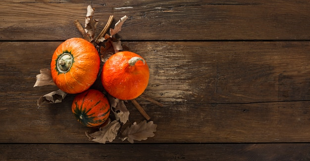 Three hokkaido pumpkins with dry autumn leaves and cinnamon sticks on wooden table