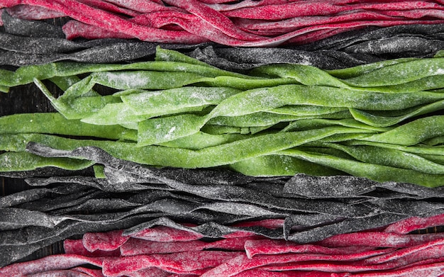 Three home-made pasta on a dark wooden table. black pasta with cuttlefish ink, green pasta with spinach and pink paste