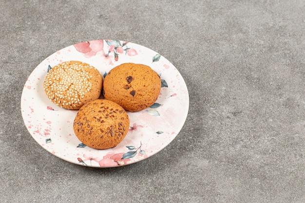 Tre biscotti freschi fatti in casa sulla zolla bianca.