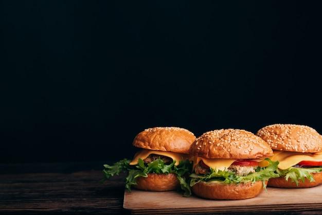 Три домашние гамбургеры с мясом, сыром, листьями салата, помидорами на деревянном столе