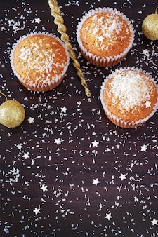 Three homemade orange muffins decorate coconut powder on dark wood