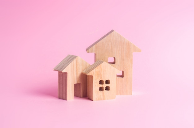 Three houses on a pink background. buying and selling of real estate, construction.