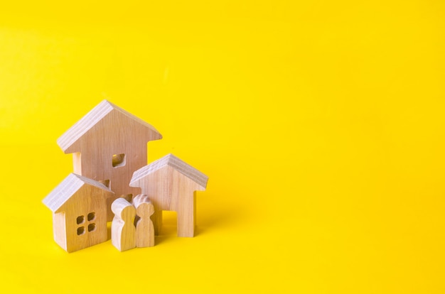 Three houses on a yellow background. buying and selling of real estate, construction.