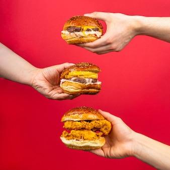 빨간 배경에 격리된 맛있는 햄버거 치즈버거 버거를 들고 있는 세 사람의 손