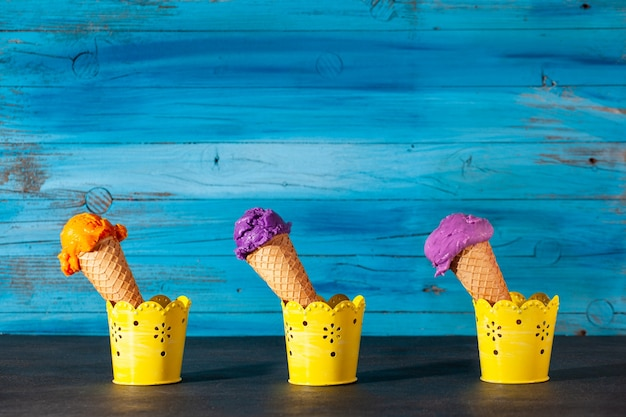 Three ice cream cones on old wooden blue wall. the scoops are assorted of blueberry,  strawberry and apricot icecream in waffles