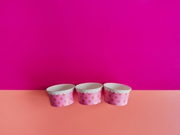 フクシアとオレンジ色の背景に分離された空の色の水玉模様の3つのアイスクリームカップ