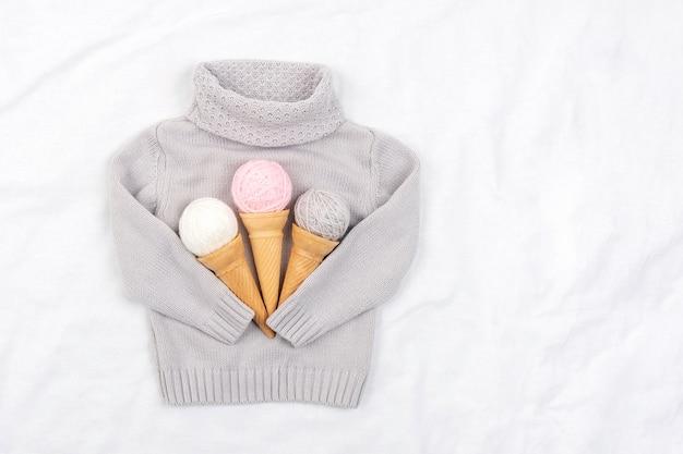 Три мороженого из клубка пряжи в вафельных рожках и серый вязаный свитер на белом фоне. вид сверху плоская планировка копирование пространства.