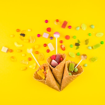 Three ice cream waffle cones with varieties of candies on yellow background