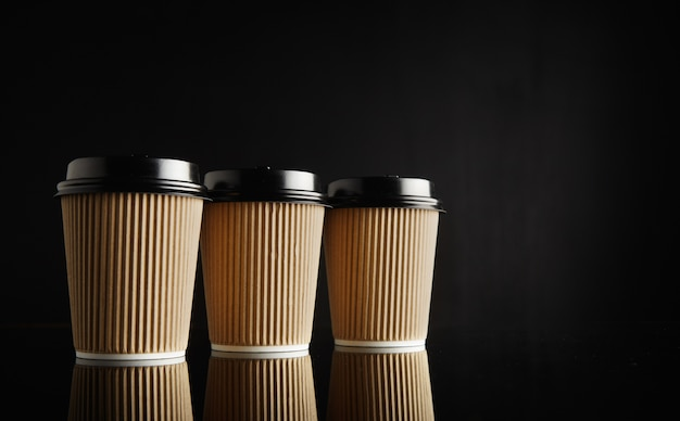 Three identical light brown cardboard takeaway coffee cups with black lids in a row on reflective black table against black wall