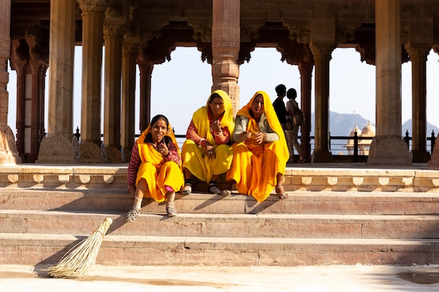 Three india woman cleaner with colourful sari having a rest sitting on stair