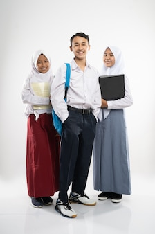 Three indonesian teenagers wearing school uniforms smile at the camera with a backpack a book and a ...