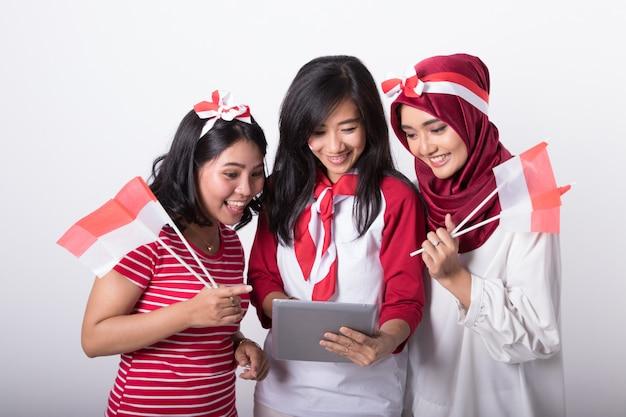 Три индонезийские женщины с помощью планшета и флаги индонезии