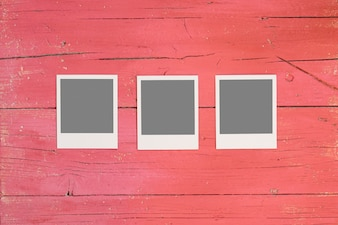 Three instant photos on wooden background