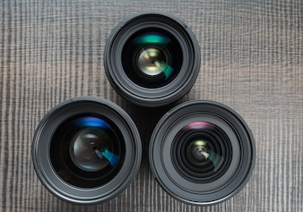 Three interchangeable camera lenses on a wooden table