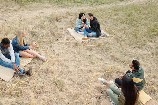 야외에서 마른 잔디에 앉아 휴식을 취하고 하루에 대한 계획을 논의하는 캐주얼웨어를 입은 세 명의 이문화 커플