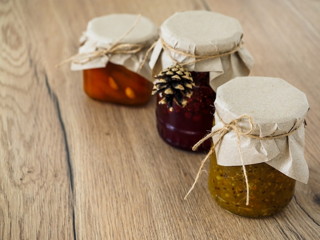 Three jars of jam on a wooden surface packed in kraft paper