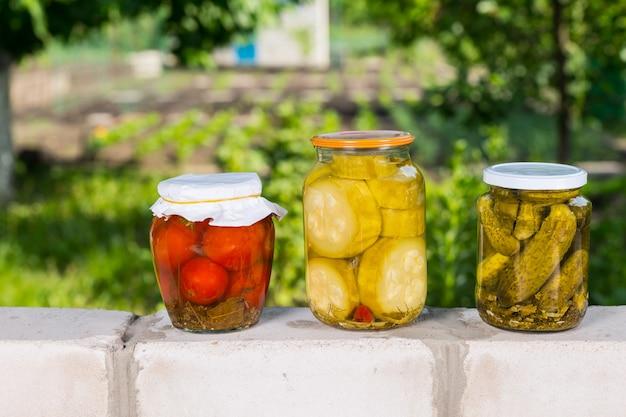 レンガの壁の上に保存されたばかりの野菜の3つの瓶-庭の前のトマト、玉ねぎ、きゅうりのピクルスの瓶