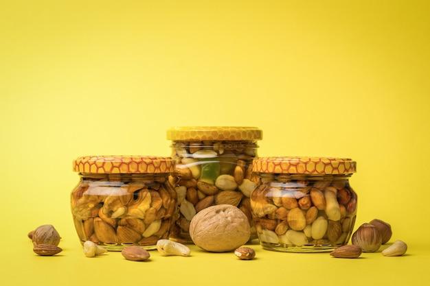 노란색 배경에 꿀과 견과류 세 병, 흩어져 있는 견과류. 천연 영양제입니다.