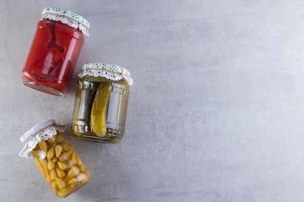 石のテーブルに置かれた漬物の3つの瓶。