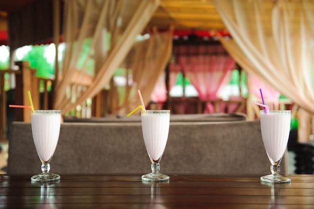 古い木製のテーブルにストローでピンクのベリーミルクセーキの3つの瓶。