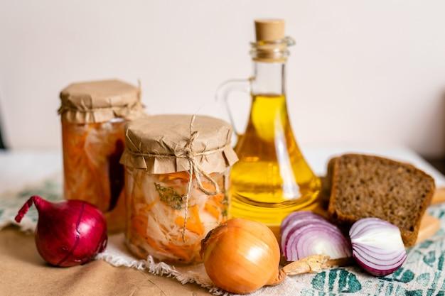 ザワークラウトとニンジンの3つのジャールと、ジュース、オイル、パン、タマネギ、白い木製のテーブルのボトル。ロシアとドイツの伝統的な自家製の発酵料理