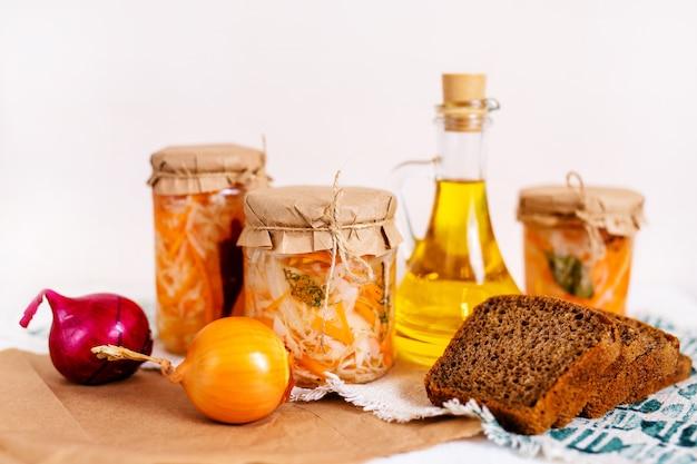 ザワークラウトとニンジンの3つのジャールと、ジュース、オイル、パン、タマネギ、白い木製のテーブルのボトル。伝統的な自家製
