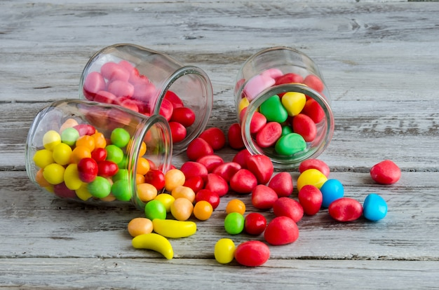 Three jars on table with scattered candies
