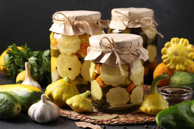 新鮮な食材を使った濃い灰色の表面にパティパン、キュウリ、ズッキーニのピクルスが入った3つの瓶、水平形式