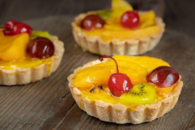 갈색 나무 테이블에 과일과 체리 3 젤리 타르트