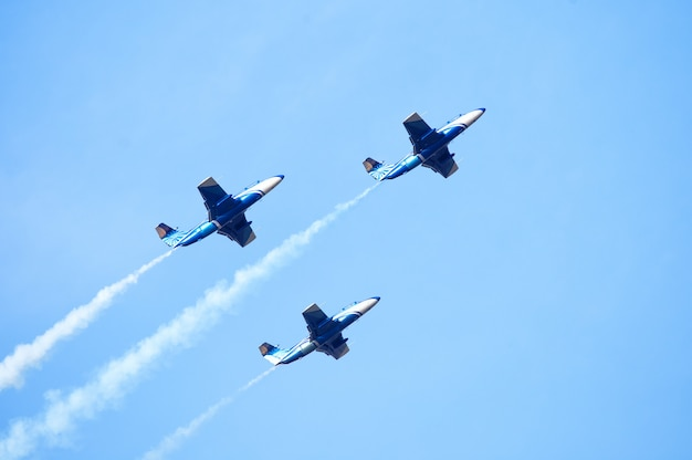 Three jet planes producing colored smoke in the sky