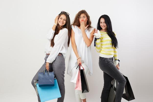 Три радостные девушки, одетые в красивую повседневную одежду, стоят с множеством сумок после покупок на белом фоне.